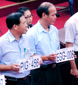Taipei City councilors holding up signs resembling license plates with funny English: PIG-456 and EGG-008