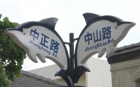 street signs reading 'JhongShan Rd.' -- note InTerCaPiTaLiZaTion -- (Zhongshan Road) and 'Jhongjheng Rd.' (Zhongzheng Road) -- no intercapping